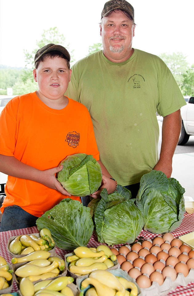 Georgia Mountain Parkway - Father and son farmers displaying their produce at the Union County Farmers Market in Blairsville, Georgia