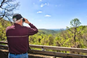 Georgia Mountain Parkway - Visitor takes in the view of Blood Mountain from the deck at Walasi-Yi in Blairsville, Georgia